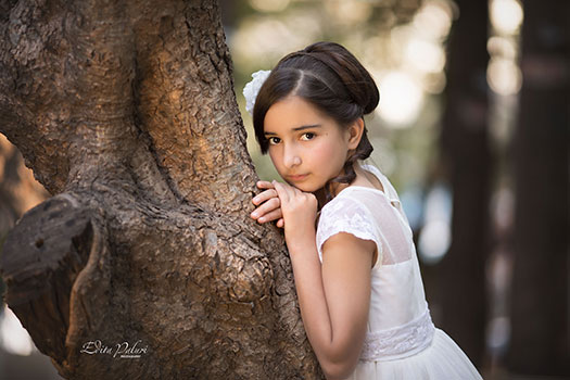 Girls in white dress portrait beside a tree