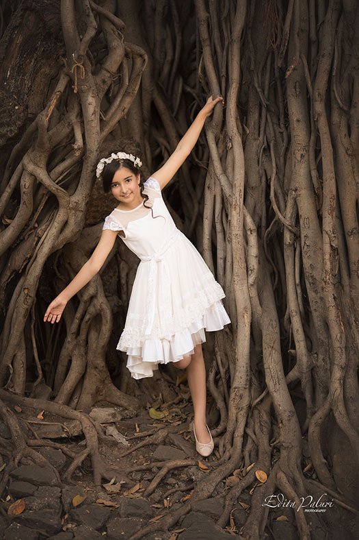 Girl in white dress beside huge banyan tree in India