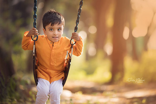boy on swings in forest