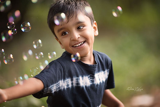 boy is playing with soap bubbles