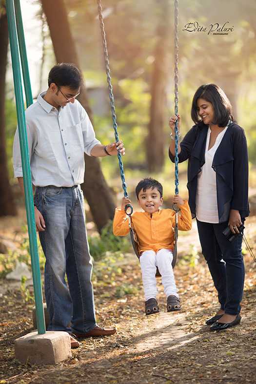 family with boy on swings in forest