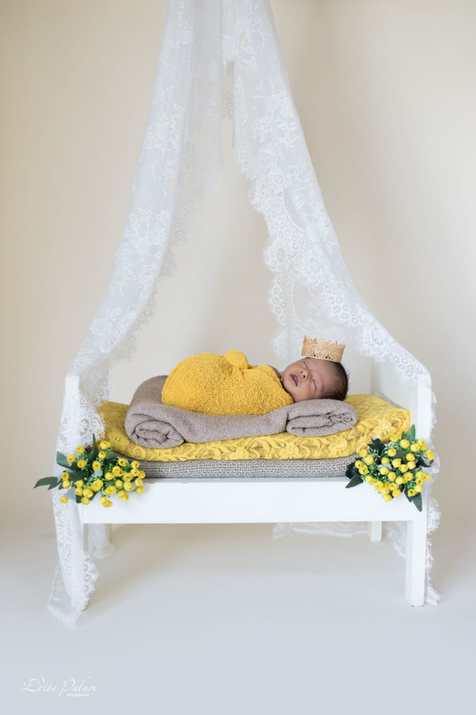 2 weeks newborn boy in yellow wrap sleeping in small bed with net on top