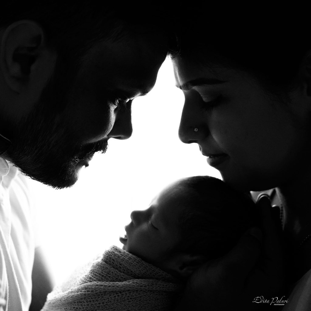 Parents holding newborn silhouette