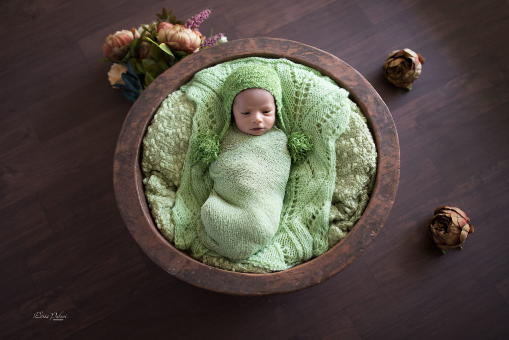 indian newborn boy in green basket
