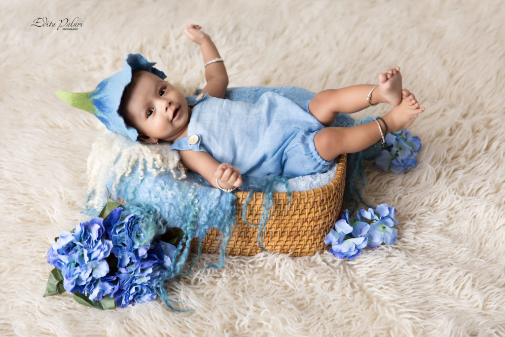happy baby boy with blue hat in basket