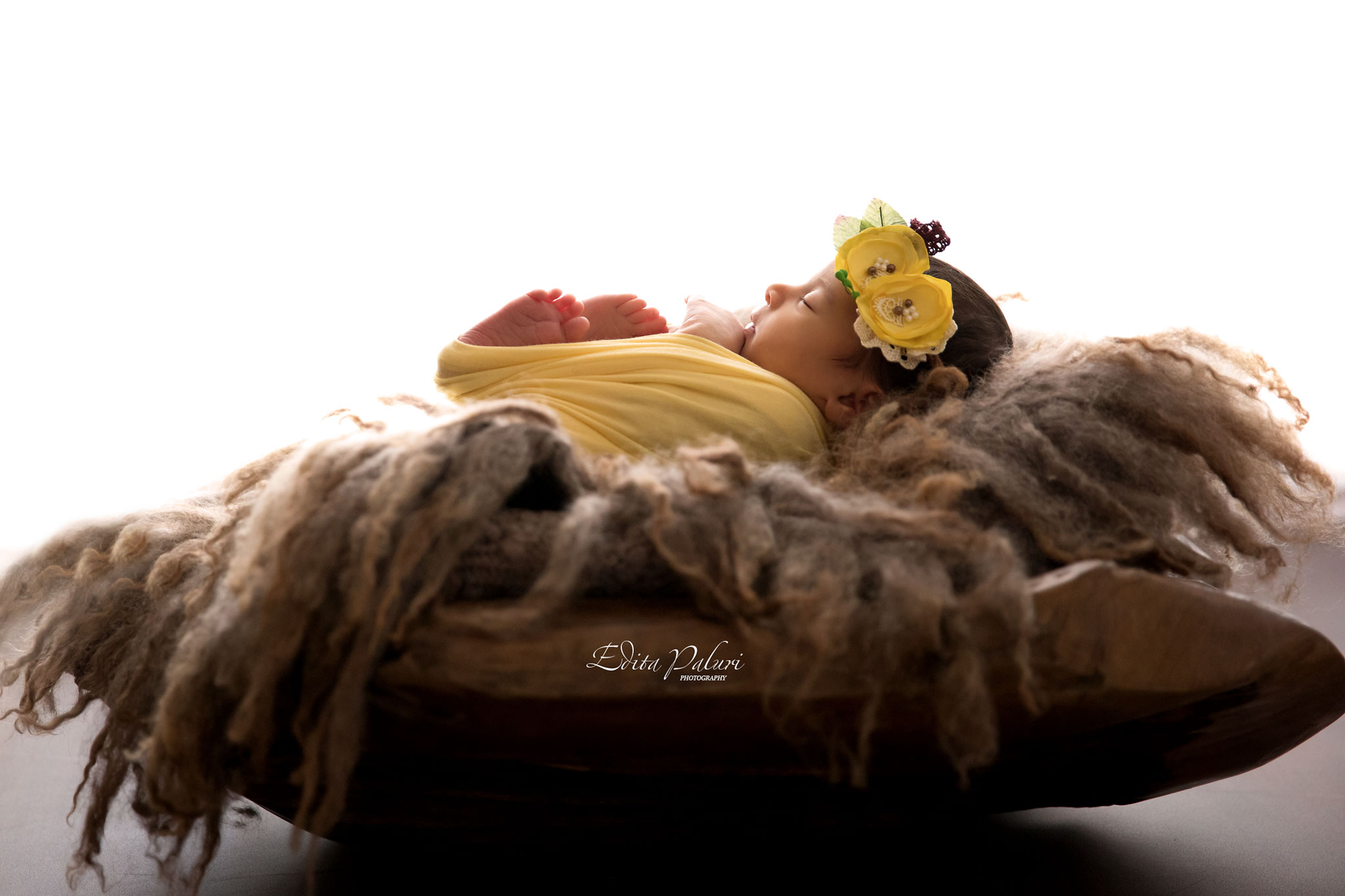 Gorgeous baby girl in yellow wrap backlit photo