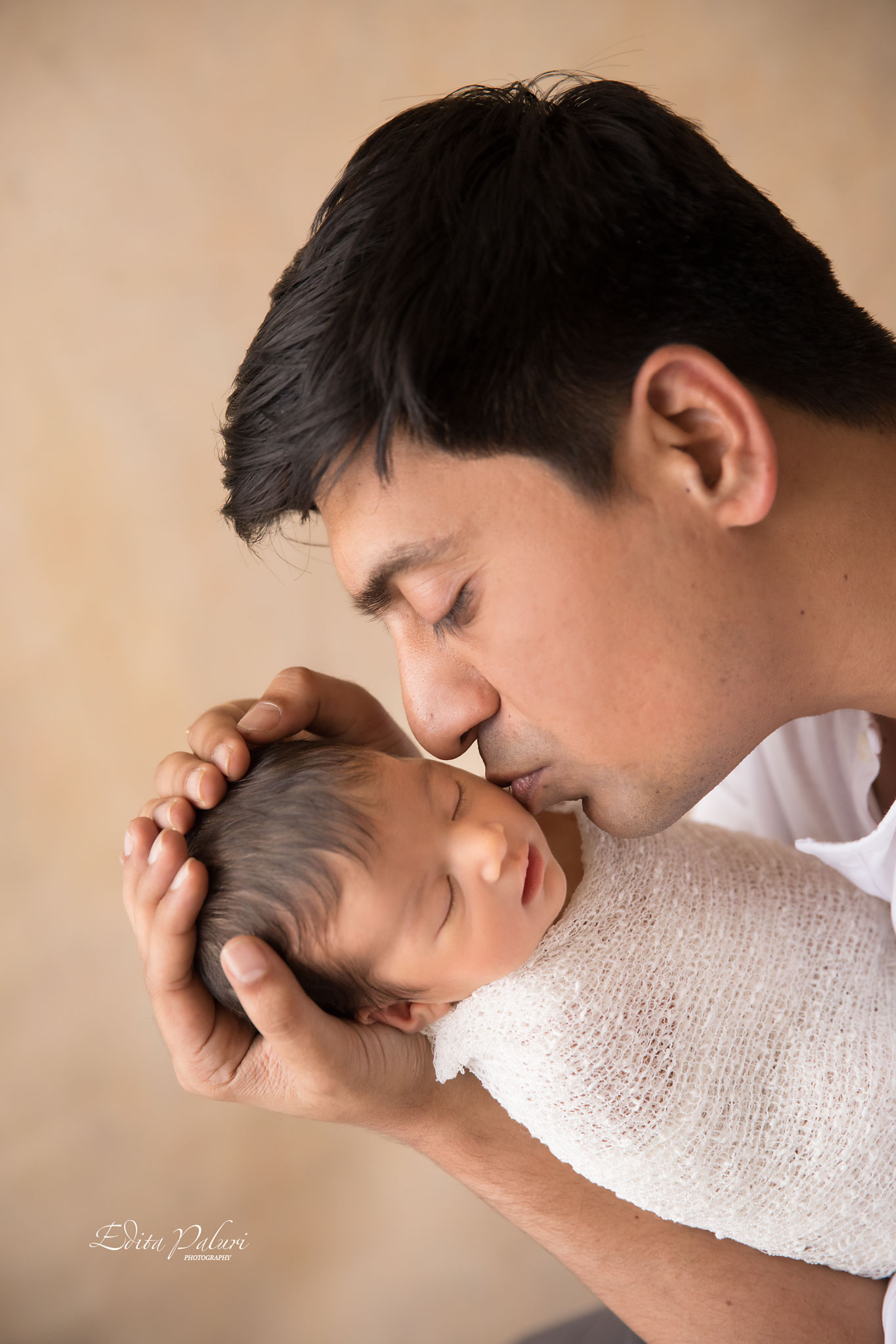 Father is kissing newborn daughter photo