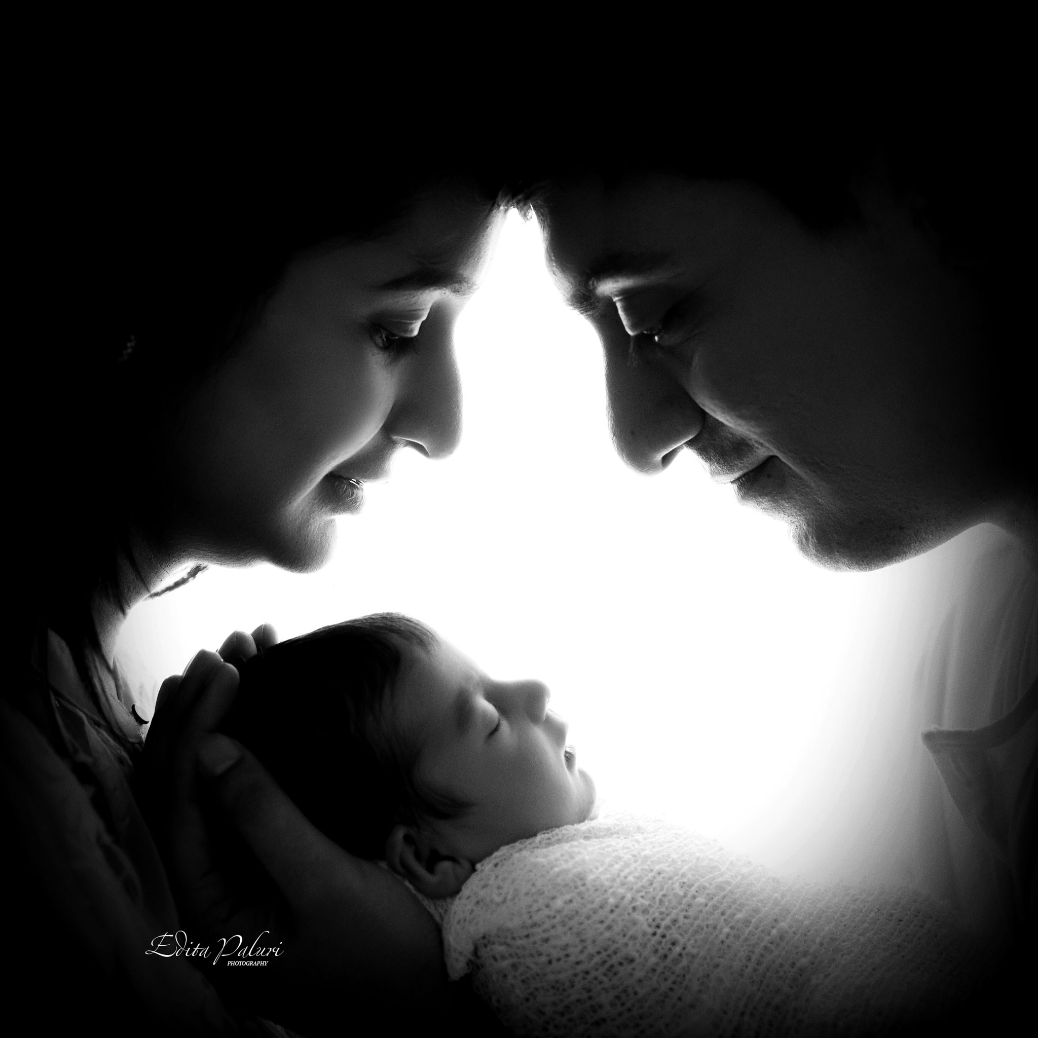 Backlit silhouette parents with newborn photo