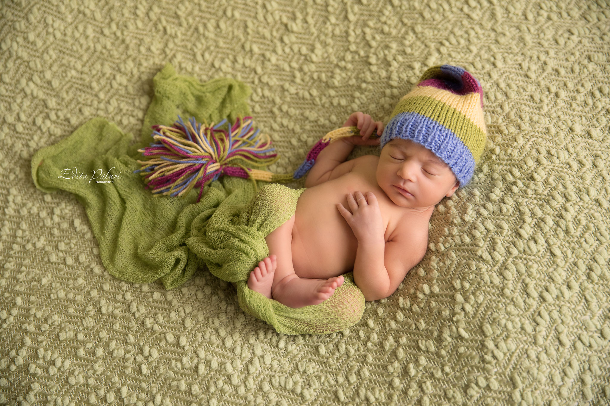 newborn girl with colorful hat sleeping