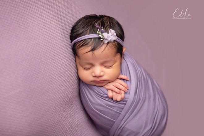 newborn baby indian girl sleeping wrapped in purple wrap
