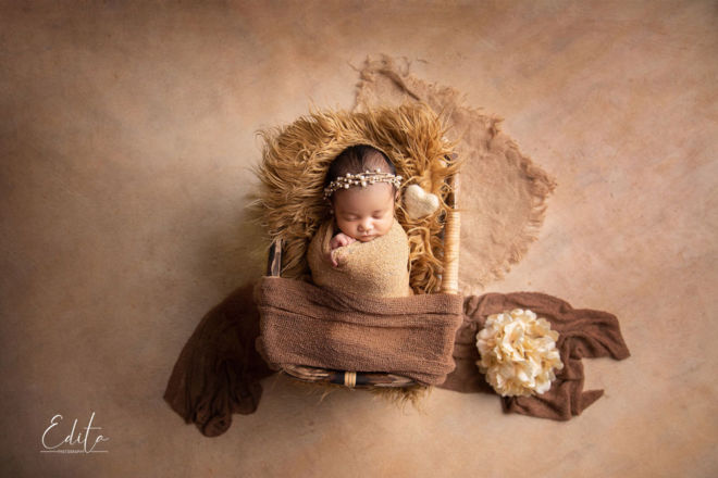 Newborn baby girl wrapped in cream wrap sleeping in bamboo basket
