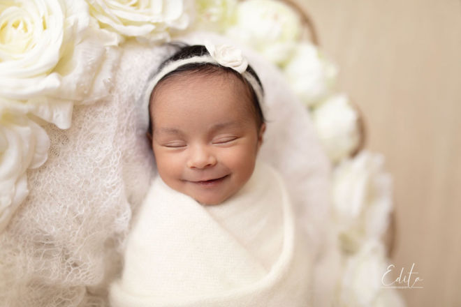 Smiling newborn baby girl in white wrap between white flowers