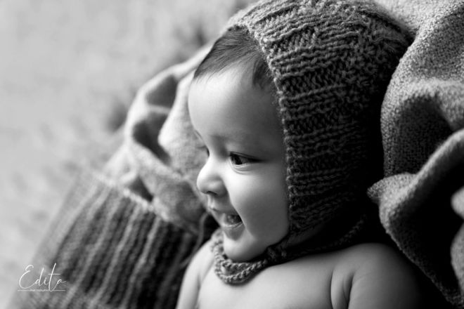 Smiling 5 month baby boy from profile in black and white photo