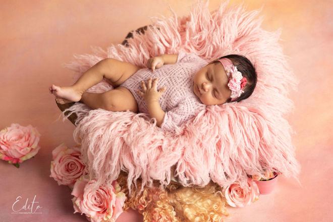 Baby girl sleeping on pink flokati photo