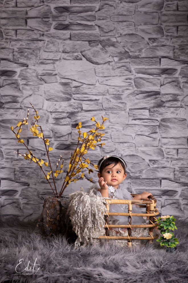 Baby girl sitting in bamboo basket with grey background and yellow flowers