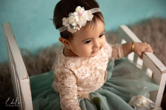 Cute baby girl in vintage cream top and turquoise skirt sitting on bed in Pune