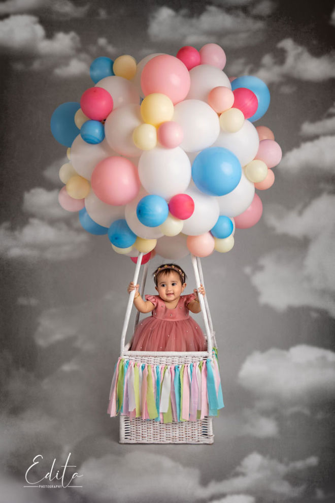 Flying hot air balloon with baby in the clouds for one year photo shoot in Pune studio