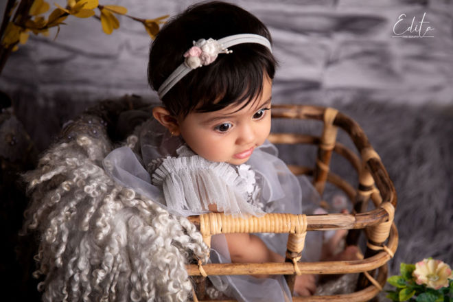 9 month baby girl sitting in bamboo basket photography in Pune