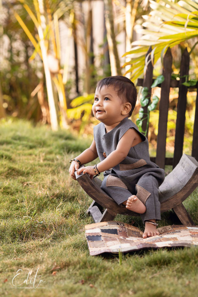 one year indian baby sitting on vintage wooden bench outdoor photo shoot in Pune