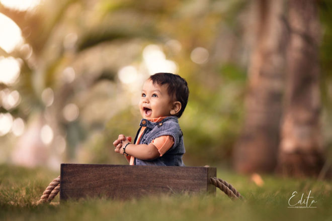 Laughing 1 year baby boy sitting in wooden vintage box in garden in Pune