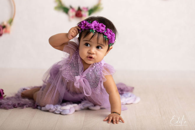 Crawling baby girl in lace purple dress trying to remove her headband in studio Pune