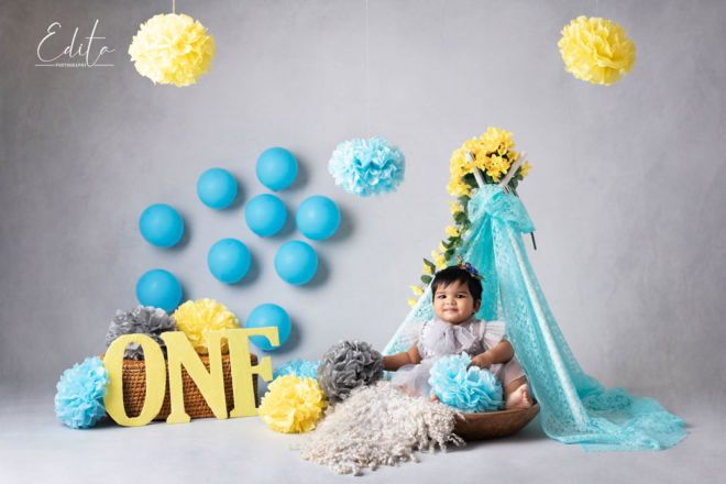 One year baby girl in grey dress in yellow, blue and grey decorations setup at studio in Pune
