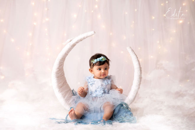 Dreamy baby girl photo shoot in moon setup with fairy lights in background