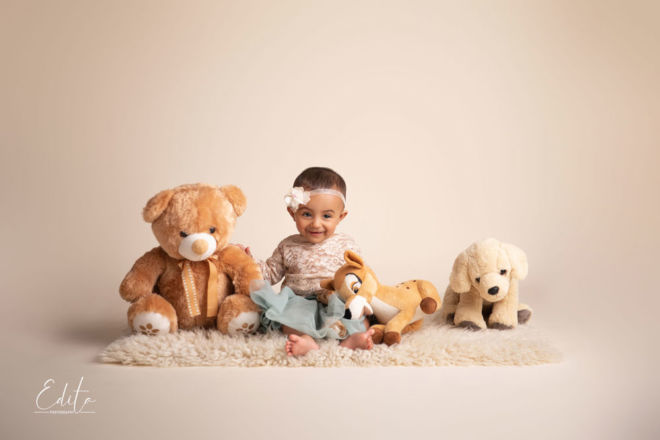 Indian smiling baby girl sitting with soft toys photo shoot in Pune studio