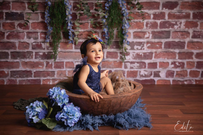 Vintage setup with one year baby girl in blue dress sitting in wooden bowl in Pune
