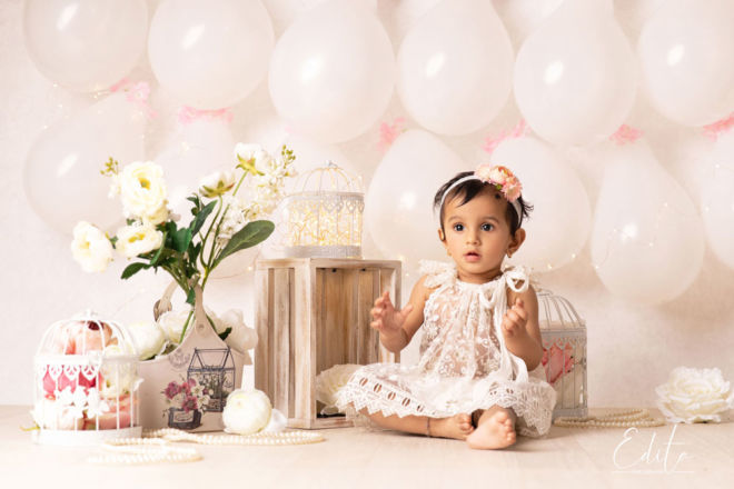 Adorable and cute one year baby girl in white creative setup with balloons and flowers