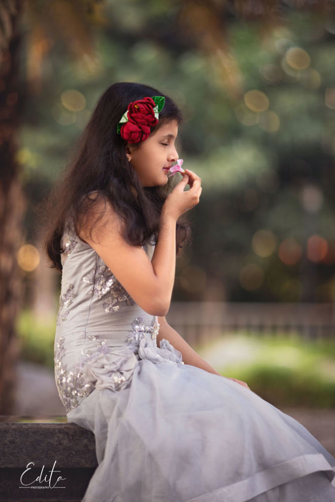 Girl with closed eyes in grey dress smelling flower in garden in Pune