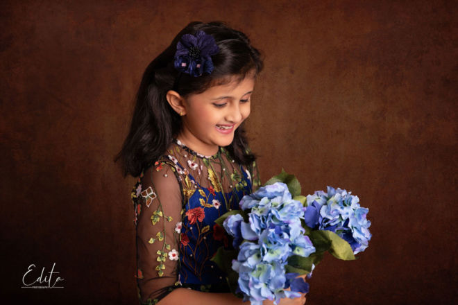 Smiling girl holding blue flowers with brown hand-painted textured canvas background
