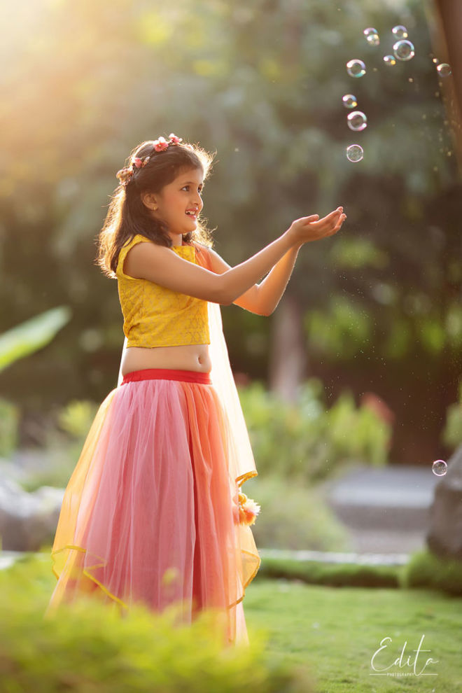 Children photo shoot - Girl in indian attire catching soap bubbles at sunset in the garden