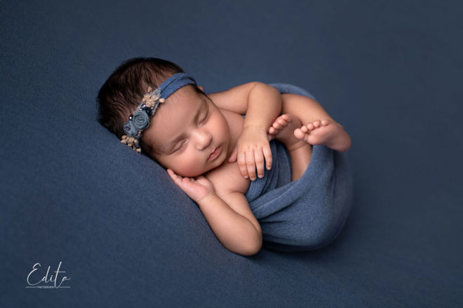 Newborn girl in blue wrap with blue handmade headband sleeping on blue blanket