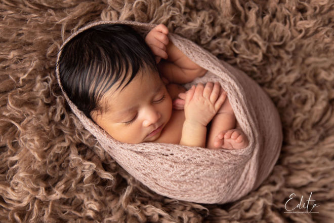 Newborn baby girl in cocoon pose relaxed and holding her foot