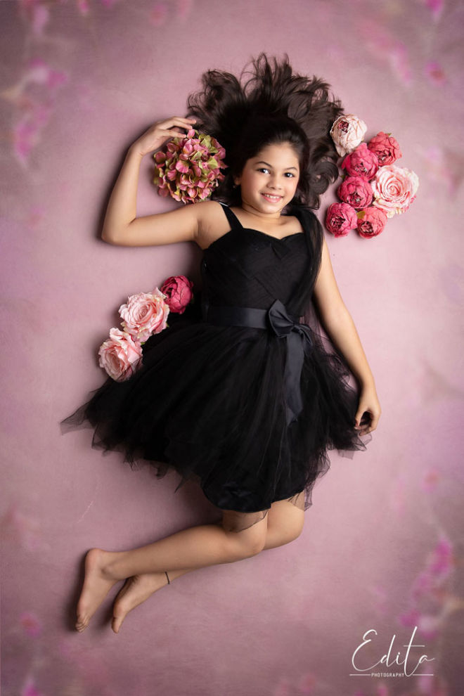 Children photo shoot - aerial girl in black dress photos with pink background and flowers