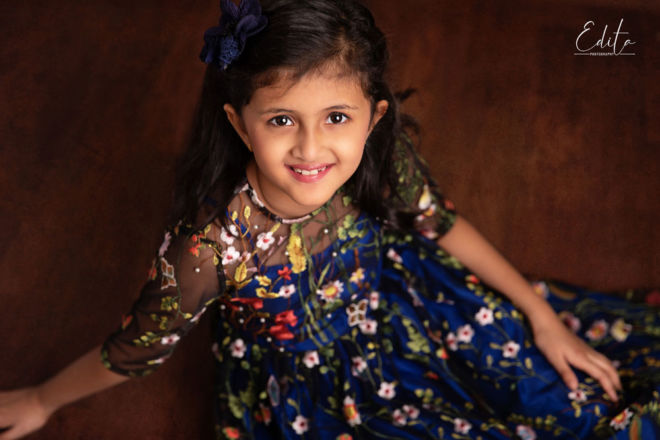 Children photo shoot - smiling girl in blue dress with flowers portrait by Edita Paluri in Pune