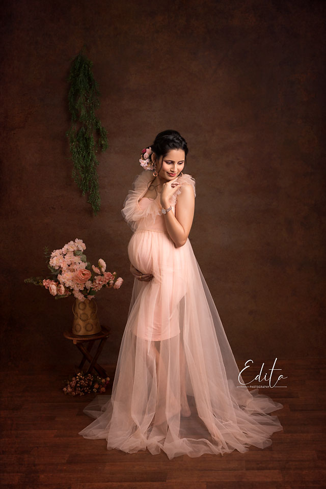 Mom to be in peach gown against brown textured canvas background in Pune studio