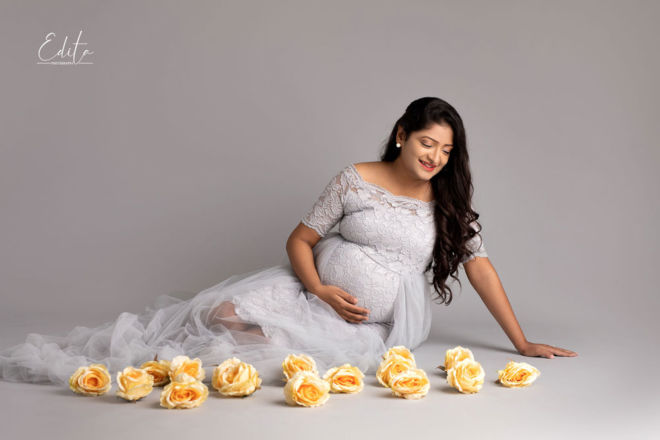 Maternity photo in grey gown with yellow flowers in Pune by Edita Photography