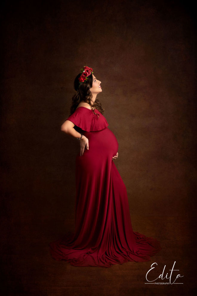 Fine art maternity photography in red gown and red flower tiara on head