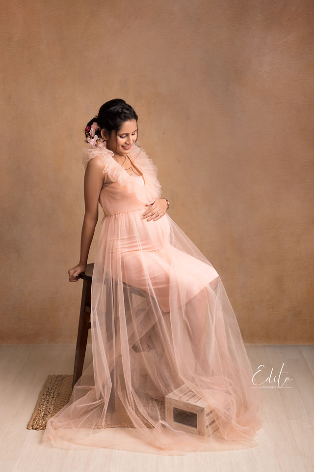Pregnant woman in peach outfit sitting on high chair in maternity photo shoot Pune