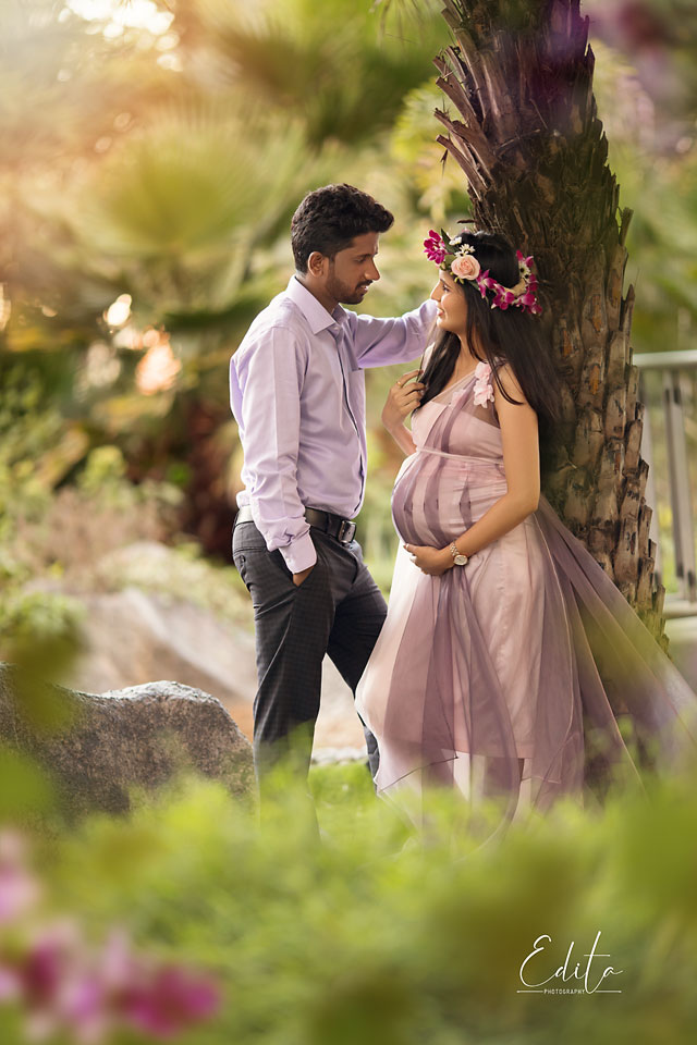 Couple expecting baby standing under the tree in garden pune