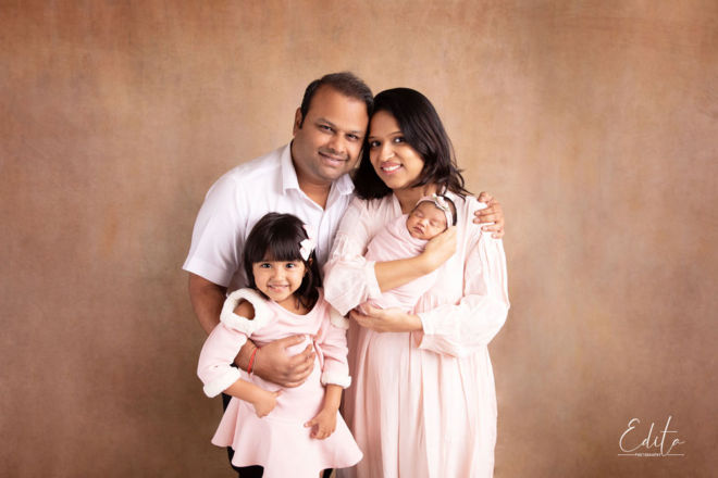 Family of 4 portrait with newborn wearing light baby pink colors and beige background