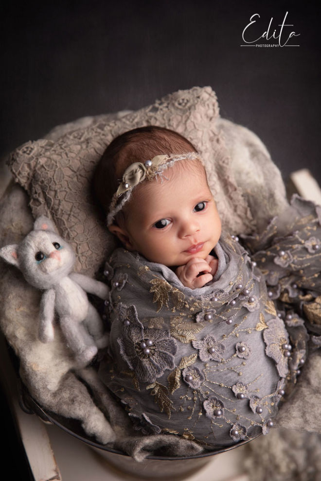 Newborn indian girl photo with open eyes wrapped in grey lace and with cute kitten