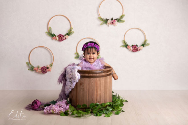Chubby one year baby girl sitting in wooden bucket photo shoot at studio in Pune