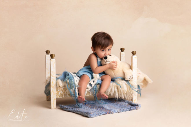 Indian baby boy playing with soft toy on white and golden bed in Pune