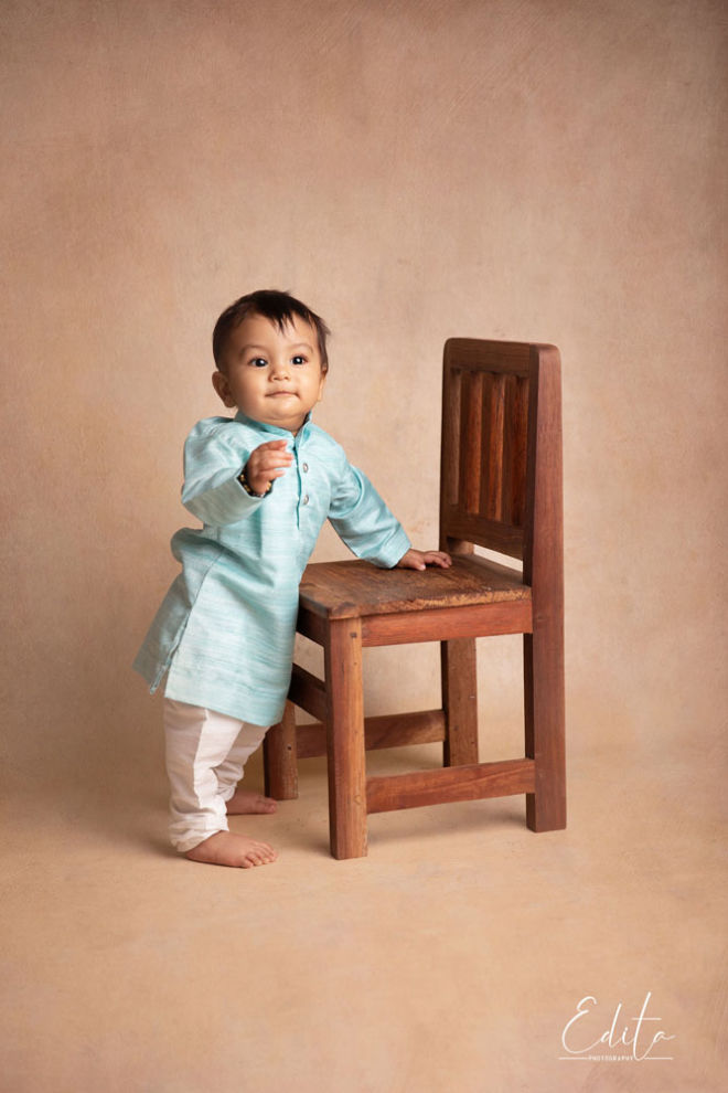 One year old baby boy in traditional indian attire standing with support of a vintage wooden chair