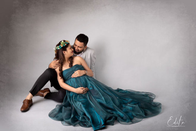 Couple posing maternity photo shoot in studio