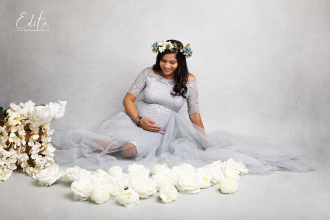 Maternity shoot with flowers on grey background with texture