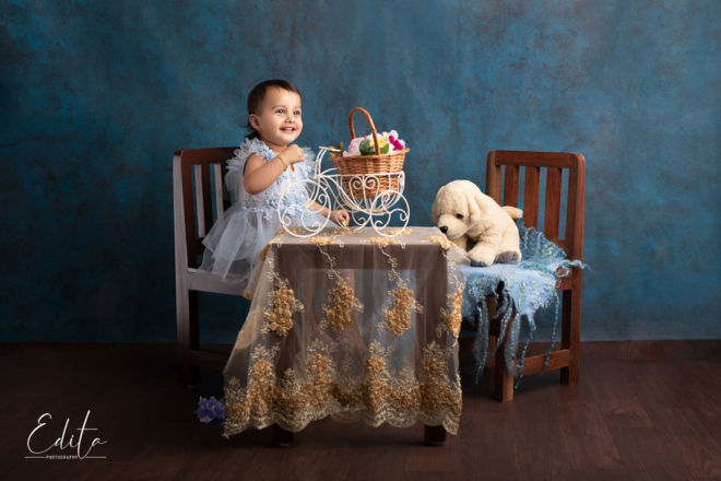 Toddler girl tea party with furry puppy toy
